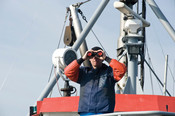 Man looking in binoculars on ship  CURRENTLY SUSPENDED