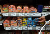 Consumers hand taking a tuna can from a shelf with tuna products at a supermarket