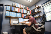 Travis Elison working at desk, Alaska Department of Fish and Game | Wild Alaska Salmon Fishery Visit, Bristol Bay