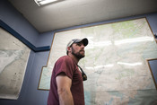 Travis Elison in front of map, Alaska Department of Fish and Game | Wild Alaska Salmon Fishery Visit, Bristol Bay