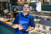 Fishmonger holding fish- fishmonger - fishcounter