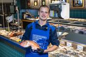 Fishmonger holding fish- fishmonger - fishcounter