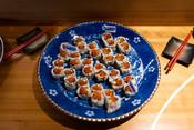 Sockeye salmon, avocado, and cucumber sushi roll topped with Ikura