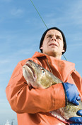 German fisherman holding fish  CURRENTLY SUSPENDED