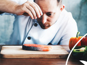 Chef assaisonne le saumon cru sur une planche à découper