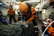 Fisheries inspection officers from the Norwegian Coastguard (Kystvakten) carrying out a fisheries inspection on a shrimp trawler in Svalbard, Norway.