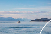 Fishing vessel on ocean with mountains and trees in background.