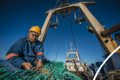 Fisherman repairing net south african Hake fishery